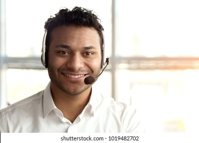 Portrait of indian operator with headset. Cheerful smiling black man face with headset in bright office.