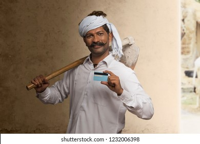 Portrait of Indian rural farmer holding credit card and carrying hoe on his shoulder