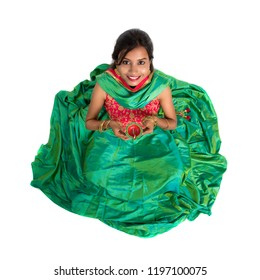 Portrait of a Indian Traditional Girl holding Diya, Girl Celebrating Diwali or Deepavali with holding oil lamp during festival. Top view over white background