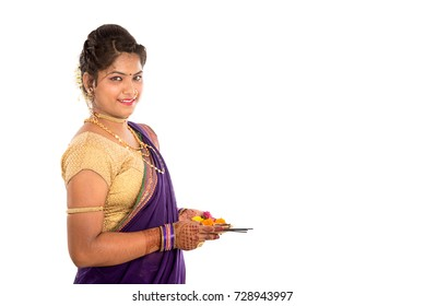 Portrait of a Indian Traditional Girl holding pooja thali with diya, Diwali or deepavali photo with female hands holding oil lamp during festival of light on white background