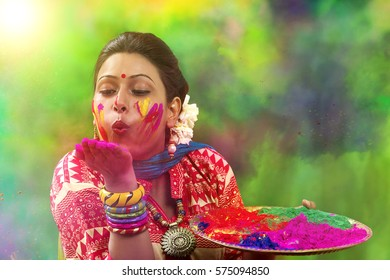 Portrait of an Indian Woman celebrating Holi by blowing Holi powder