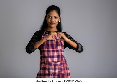 Portrait of Indian woman chef or cook in an apron, presenting, pointing, with ok sign, thumbs up on the grey background.