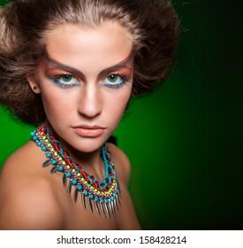 Portrait of indian woman. Green background, studio shot.