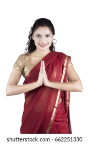 Portrait of indian woman smiling at the camera with welcoming pose, isolated on white background