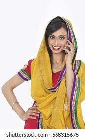 Portrait of an Indian woman in traditional wear answering phone call over gray background