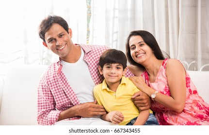 Portrait of Indian/Asian happy and young family, sitting over sofa at home