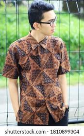 Portrait of an Indonesian young man wearing a shirt of batik cloth