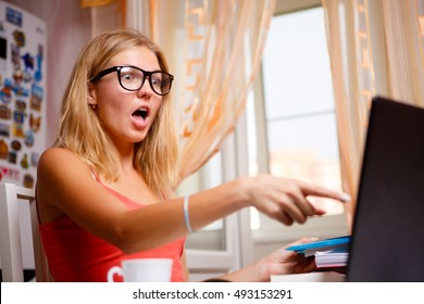 Portrait indoor of stunned student girl in glasses showing something on screen
