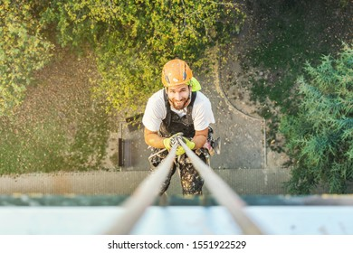 Portrait of Industrial rope access worker hanging from the building while painting the exterior facade wall. Industrial alpinism concept image. Top view. Looking straight to camera