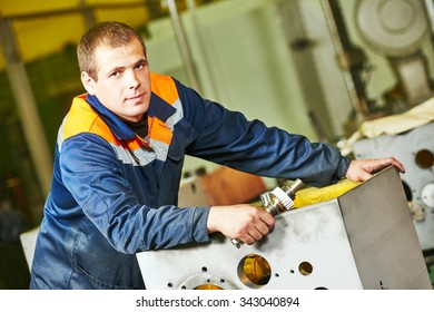 Portrait of industrial worker assembling the reduction gear box on production line manufacturing workshop