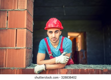 portrait of industrial worker on construction site, sitting and relaxing after a hard day at work. Brick mason worker with protective gear