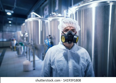 Portrait of industrial worker technologist wearing hazmat suit in production plant. Man in white protective uniform with hairnet and protective mask handling hazardous chemicals.