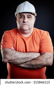 Portrait of an industrial worker wearing helmet and hands folded on chest. Portrait over black background, studio shoot.