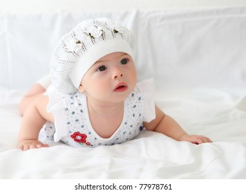 portrait of an infant baby girl wearing a hat