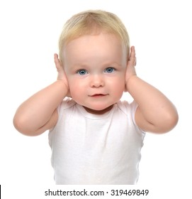 Portrait of infant child baby toddler sitting closed her hands over ears and hears nothing isolated on a white background