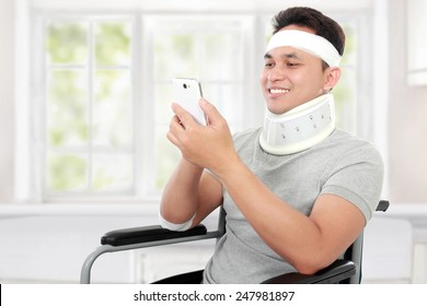 portrait of injured young man play on his smartphone