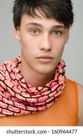 Portrait of an innocent handsome man posing fashion with colored scarf. Young guy with cool messy hairstyle.