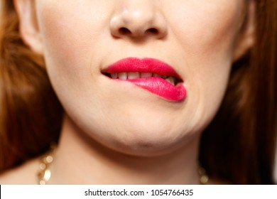 Portrait of insecure woman having doubts. Dubious redhead girl thinking, biting lips. Close up of mouth