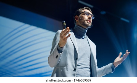 Portrait of Inspirational Innovative Speaker, Talking about Happiness, Self, Success, Empowerment, Efficiency and How to Be More Productive Self. Large Conference Hall with Cinematographic Light