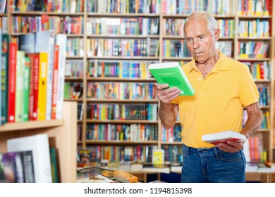 Portrait of intelligent friendly glad  man choosing necessary books on shelves in library