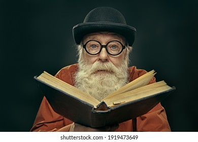 Portrait of an intelligent old man in glasses and bowler with a long gray beard holding an old big book and looking at the camera. Old age wisdom.