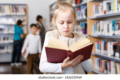 Portrait of intelligent preteen girl browsing textbooks in school library