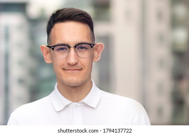 Portrait of intelligent smart guy in glasses and white shirt. Young man, student looking at camera and smiling.