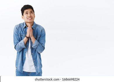Portrait of intense young worried asian man nervously praying for dream come true, talking to God, press hands together in pray raising head in the sky to plead, begging, standing white background