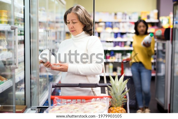 Portrait of interested elderly woman shopping in supermarket, choosing fresh dairy products on refrigerated shelves