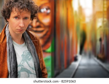 Portrait of an interesting looking man outdoors against colorful urban setting