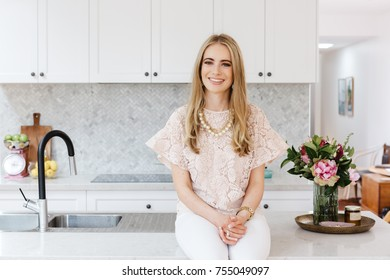 Portrait of an interior designer sitting on a kitchen bench