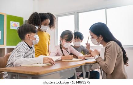 Portrait der internationalen kaukasischen und asiatischen Schüler Lehrer mit Gesichtsmaske in der Gruppenstudie, Selbstschutz vor dem Koronavirus nach Abklingen. Neue Normalität, zurück zum Schulkonzept
