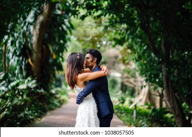 Portrait of interracial couple taking wedding photos in a beautiful park in the day. An Indian man and his Chinese fiance are passionately kissing as they hold hands on a pathway.