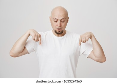 Portrait of intrigued bald european bearded man pointing down and looking at floor as if seeing something surprising, standing against gray background in white t-shirt. Guy looks from balcony