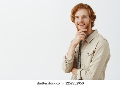 Portrait of intrigued and curious redhead happy guy receiving intersting offer consedering to except it rubbing beard and smiling broadly at camera thinking, making decision or choice