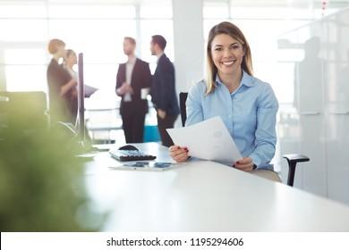 Portrait of investment advisor businesswoman sitting at office.