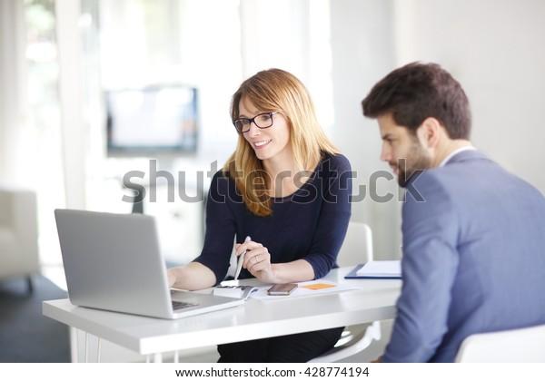Portrait von Anlageberaterin im Büro vor dem Computer und Beratung mit jungen Profi-Mann.