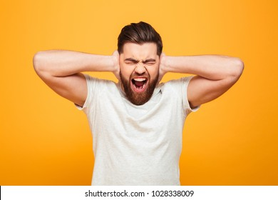Portrait of an irritated bearded man covering ears and screaming isolated over yellow background