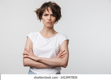 Portrait of irritated woman with short brown hair in basic t-shirt frowning and looking at camera isolated over white background