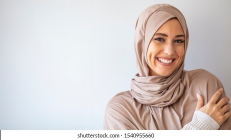Portrait of islamic woman smiling. Pretty muslim girl. Beautiful asian muslimah woman model posing on grey wall studio. Portrait Of Arab Beauty.