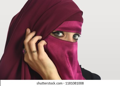 Portrait of Islamic woman wearing veil isolated over light background