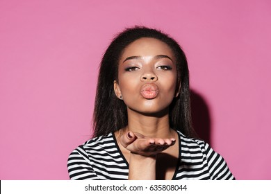 Portrait of a isolated over pink background beautiful young african woman blowing kiss to camera