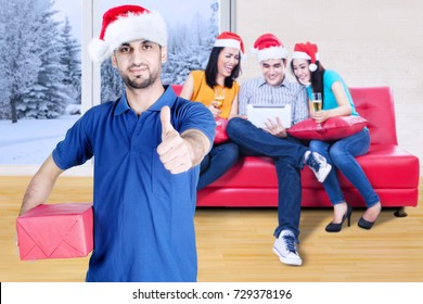 Portrait of Italian courier is showing thumb up while delivering a Christmas package to his customers