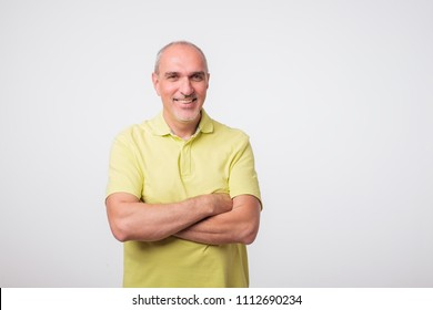 portrait of italian mature man in yellow shirt. He is standing condident on gray background.