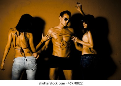 Portrait of jealous people. Handsome man in between two sexy woman