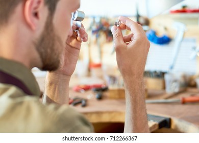 Portrait of jeweler inspecting ring through magnifying glass in workshop