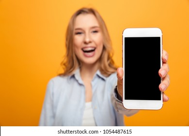 Portrait of a jooyful young girl with braces showing blank screen mobile phone isolated over yellow background