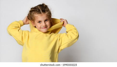 Portrait of a joyful active little girl wearing a hood on a white background. Happy cute child in a yellow sports hoodie white background. Sportswear advertising concept. Banner.
