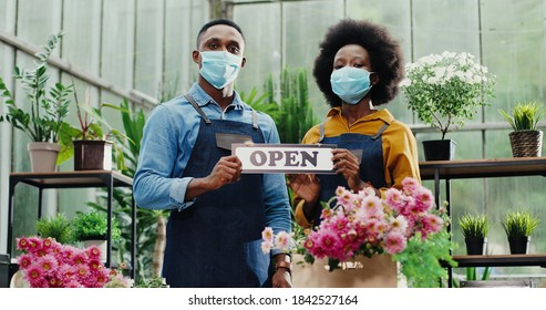 Portrait of joyful African American male and female in masks standing in flower shop and holding Open sign. Woman and man florists workers looking at camera in good mood. Family business concept