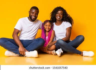 Portrait of joyful african family with cute little daughter sitting on floor and smiling at camera over yellow studio background.